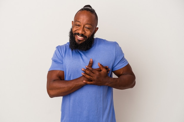 African american man with beard isolated on pink background has friendly expression, pressing palm to chest. love concept.