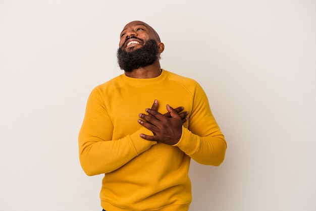 African american man with beard isolated on pink background laughing keeping hands on heart, concept of happiness.
