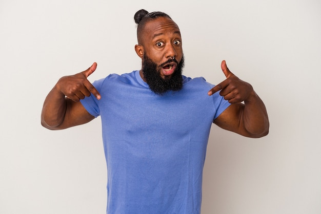 African american man with beard isolated on pink background points down with fingers, positive feeling.