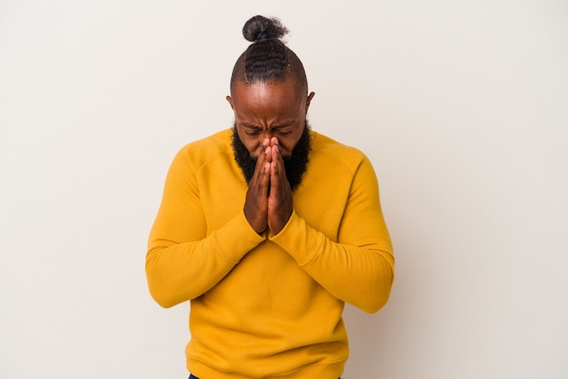 African american man with beard isolated on pink background praying, showing devotion, religious person looking for divine inspiration.