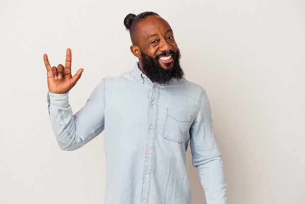 African american man with beard isolated on pink background showing a horns gesture as a revolution concept.