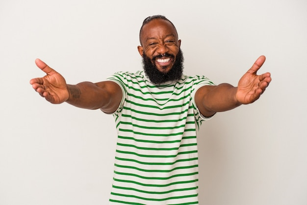 African american man with beard isolated on pink wall feels confident giving a hug