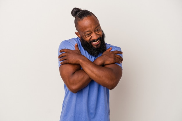 African american man with beard isolated on pink wall hugs, smiling carefree and happy.