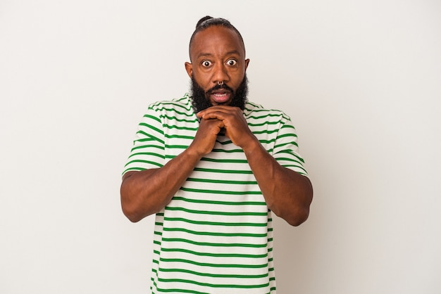 African american man with beard isolated on pink wall praying for luck, amazed and opening mouth looking to front.