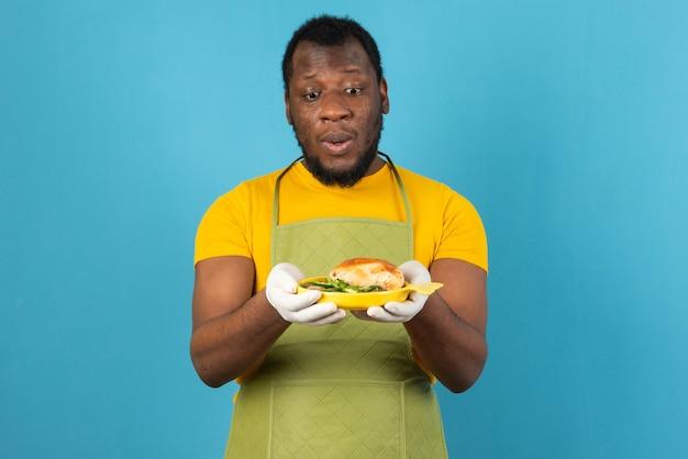 Афро-американский мужчина с бородой, в фартуке с желтой тарелкой сэндвича в руках, стоит над синей стеной.