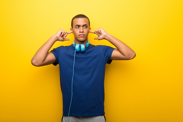 African american man with blue t-shirt on yellow background covering both ears with hands