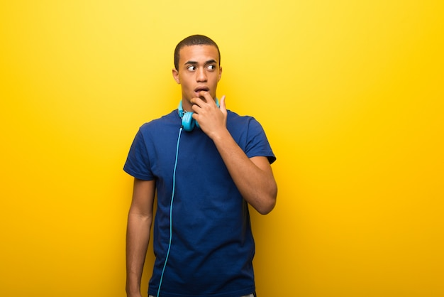 African american man with blue t-shirt on yellow background having doubts while looking up