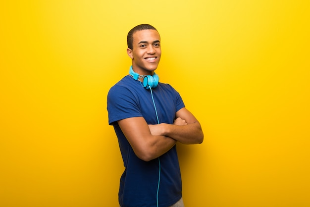 African american man with blue t-shirt on yellow background keeping the arms crossed