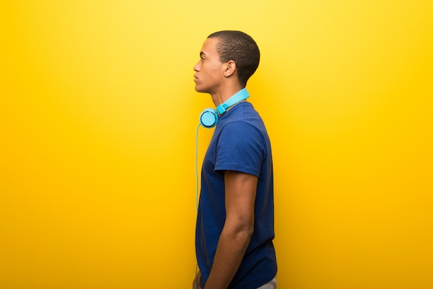 African american man with blue t-shirt on yellow background in lateral position