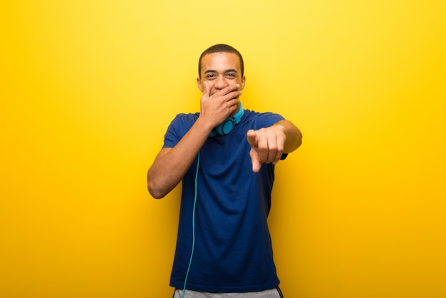 African american man with blue t-shirt on yellow background pointing with finger
