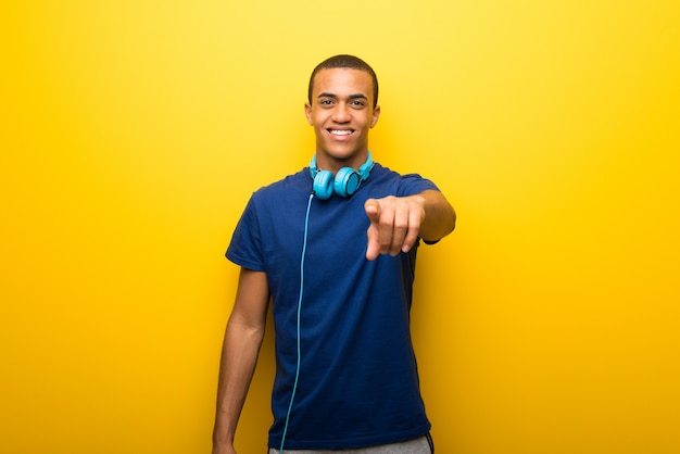 African american man with blue t-shirt on yellow background points finger at you with