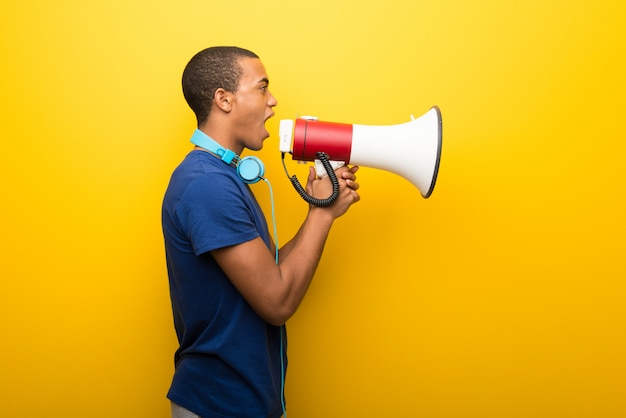 African american man with blue t-shirt on yellow background shouting through