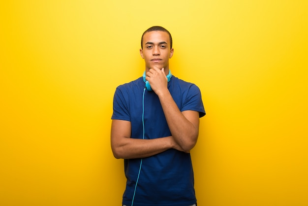 African american man with blue t-shirt on yellow background smiling and looking to the front