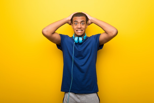 African american man with blue t-shirt on yellow background takes hands on head because has migraine