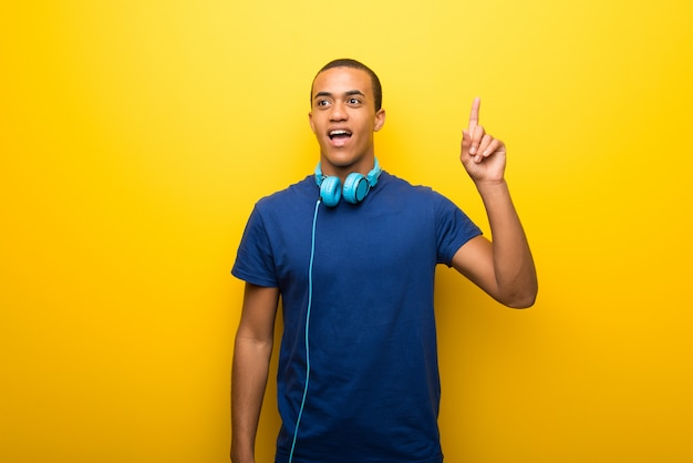 African american man with blue t-shirt on yellow background thinking an idea pointing the finger up