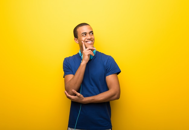 African american man with blue t-shirt on yellow background thinking an idea while looking up