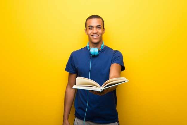 African american man with blue t shirt on yellow wall holding a book and giving it to someone