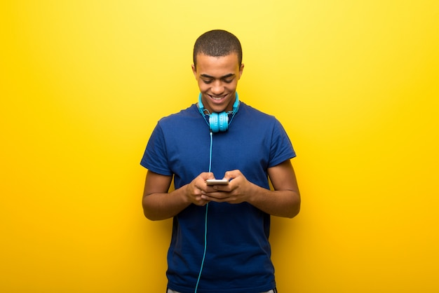 African american man with blue t shirt on yellow wall sending a message or email with the mobile