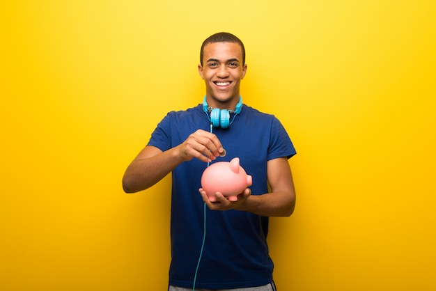African american man with blue t-shirt on yellow wall taking a piggy bank and happy because it is full
