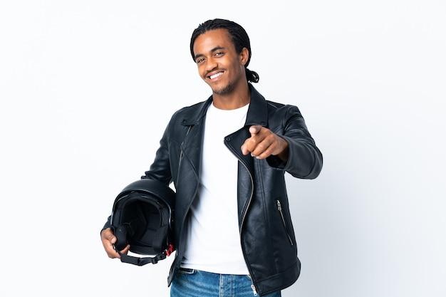 幸せな表情で正面を向いて白い背景で隔離のオートバイのヘルメットを保持している三つ編みを持つアフリカ系アメリカ人の男