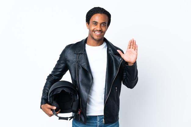 幸せな表情で手で敬礼する白い背景で隔離のオートバイのヘルメットを保持している三つ編みを持つアフリカ系アメリカ人の男