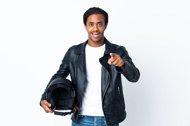 白にオートバイのヘルメットを保持し、驚いて正面を向いている三つ編みのアフリカ系アメリカ人の男