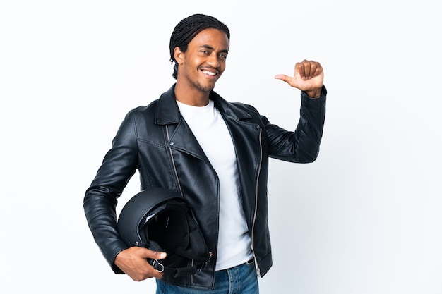 African american man with braids holding a motorcycle helmet isolated on white background proud and self-satisfied