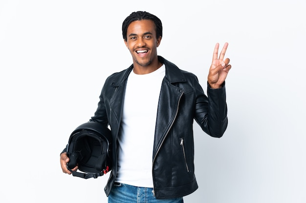 African american man with braids holding a motorcycle helmet isolated on white smiling and showing victory sign