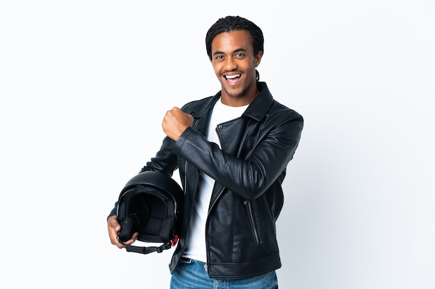 African american man with braids holding a motorcycle helmet isolated on white wall celebrating a victory