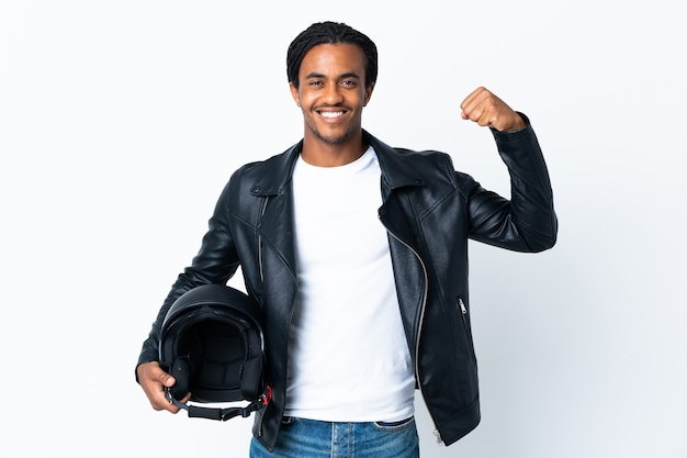 African american man with braids holding a motorcycle helmet isolated on white wall doing strong gesture