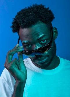 Uomo afroamericano con la pittura del viso indossando occhiali da sole