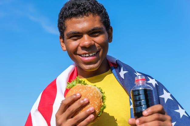 햄버거와 콜라 음료를 야외에서 즐기는 깃발을 가진 아프리카계 미국인 남자