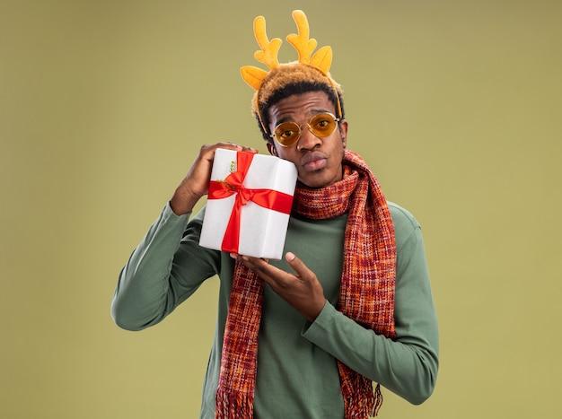 녹색 배경 위에 서 혼란 스 러 워 카메라를보고 크리스마스 선물을 들고 목 주위에 사슴 뿔과 스카프와 함께 재미있는 테두리와 아프리카 계 미국인 남자