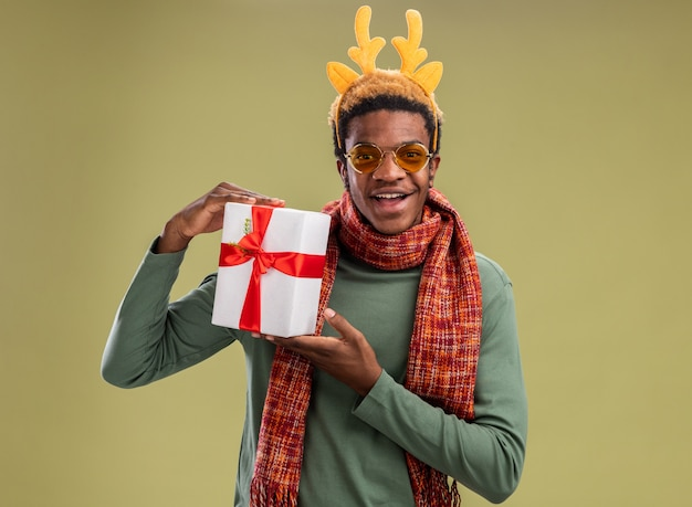 African american man with funny rim with deer horns and scarf around neck holding christmas present looking at camera with smile on face standing over green background