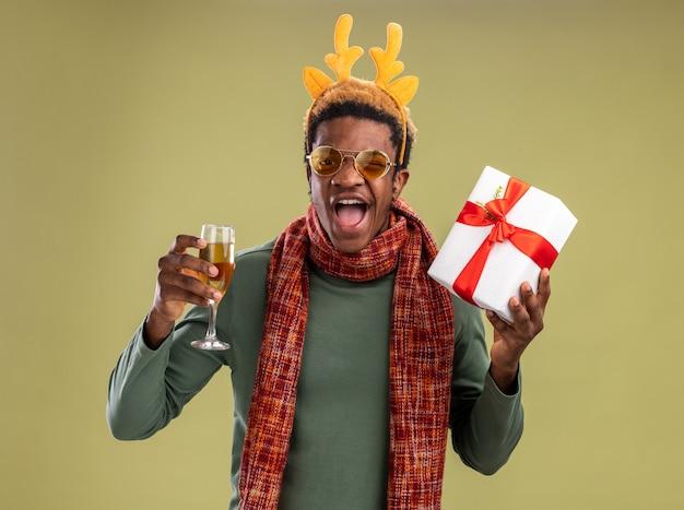 Uomo afroamericano con bordo divertente con corna di cervo e sciarpa intorno al collo che tiene un bicchiere di champagne e regalo di natale che guarda l'obbiettivo felice ed eccitato in piedi su sfondo verde