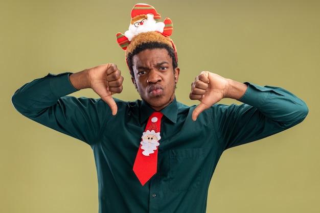 Афро-американский мужчина с забавным ободком санта-клауса и красным галстуком показывает палец вниз с сердитым лицом, стоящим над зеленой стеной