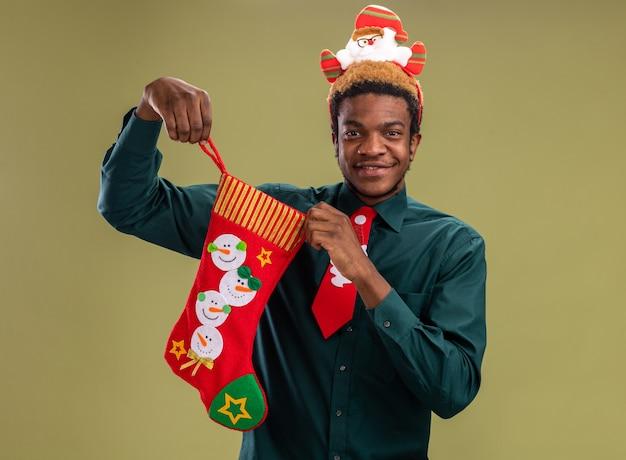 Uomo afroamericano con orlo divertente della santa e cravatta rossa che tiene la calza di natale che guarda l'obbiettivo sorridente felice e positivo che sta sopra fondo verde