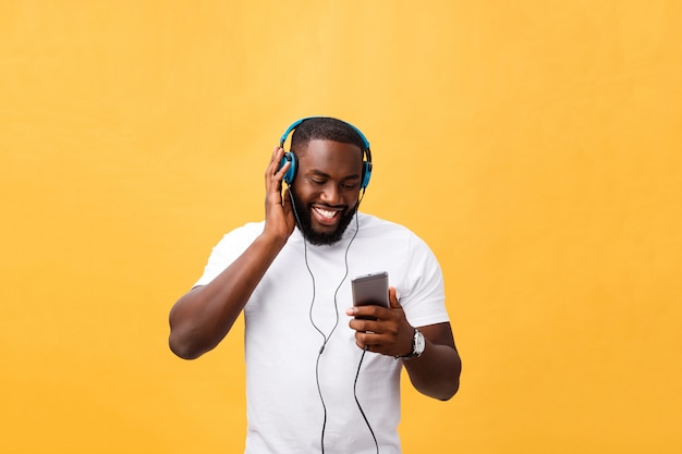 African american man with headphones listen and dance with music. isolated on yellow background