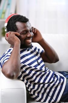 部屋のソファにヘッドフォンを持っているアフリカ系アメリカ人の男