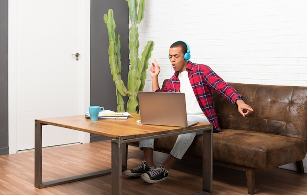 African american man with laptop in the living room listening to music with headphones and dancing