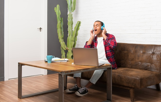 African american man with laptop in the living room listening to music with headphones