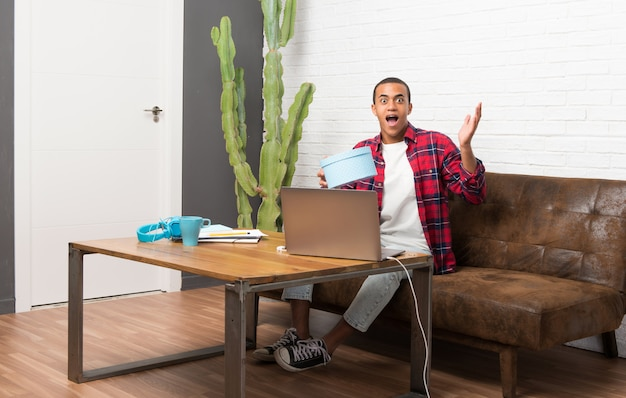 African american man with laptop in the living room surprised because has been given a gift