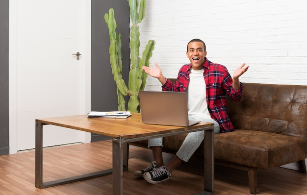 African american man with laptop in the living room with surprise and shocked facial expression