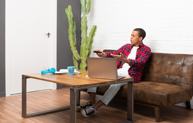 African american man with laptop in the living room with a television remote