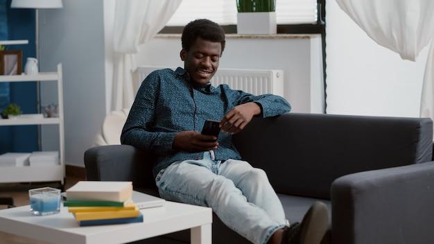 Афро-американский мужчина с телефоном в руках смотрит на контент потоковых онлайн-сервисов, наслаждаясь работой ...