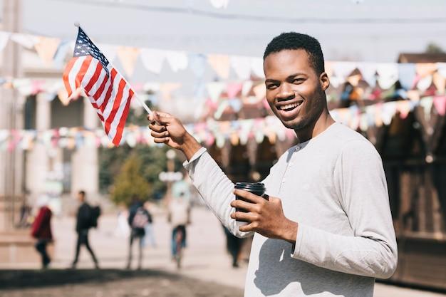 祭りにアメリカ国旗を持つアフリカ系アメリカ人の男