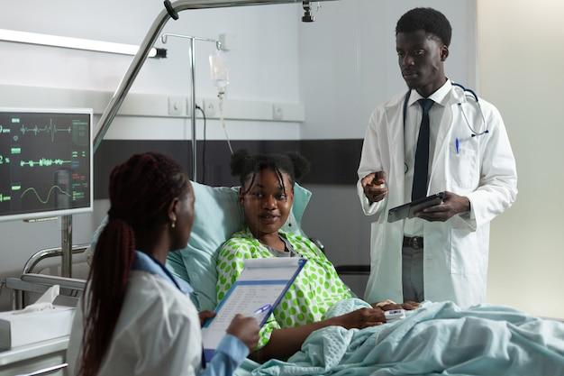 Uomo e donna afroamericani che parlano con una ragazza in corsia ospedaliera del trattamento e della diagnosi di guarigione. medici che esaminano un giovane paziente malato con collare cervicale seduto a letto