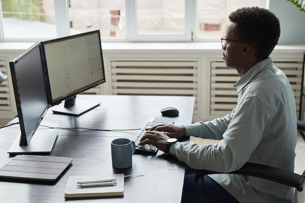 Афро-американский мужчина, работающий за столом