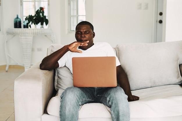 アフリカ系アメリカ人の家で働いているフリーランサーのラップトップ