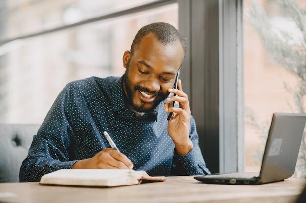 ノートパソコンの後ろで働いて電話で話しているアフリカ系アメリカ人の男。カフェに座っているひげを持つ男。